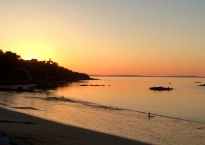 Des activités nautiques. Stand Up Paddle au coucher du soleil sur la plage - GlazOcean.com