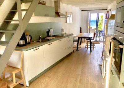 La cuisine du Beach House est très bien équipée et l'accès direct au jardin permet de facilement prendre les repas dehors face à l'ocean.
